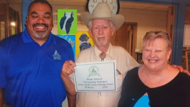 Doyle Lemond (center) receives a certificate recognizing his volunteer work at the Sears Park Senior Activity Center. He is pictured with Al Flores and Neva Gray.