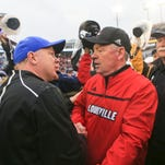 Louisville head coach Bobby Petrino meets with Kentucky's Mark Stoops after the Cards beat the Wildcats 38-24 Saturday in the Governor's Cup game at Commonwealth Stadium.