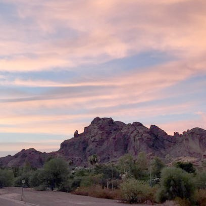 The morning sky brightens as the sun rises over Camelback