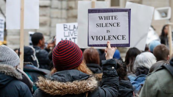 Un grupo de personas protestan contra tiroteos policiales contra minorías desarmadas en los EU.