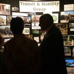 Lauren Short, 13, left, smiles at Denise Freestone, center, and her husband, Bruce, in front of an exhibit for the Transit and Mobility Group during a celebration of the UniverCity report at the Hilton Fort Collins in this 2007 file photo.