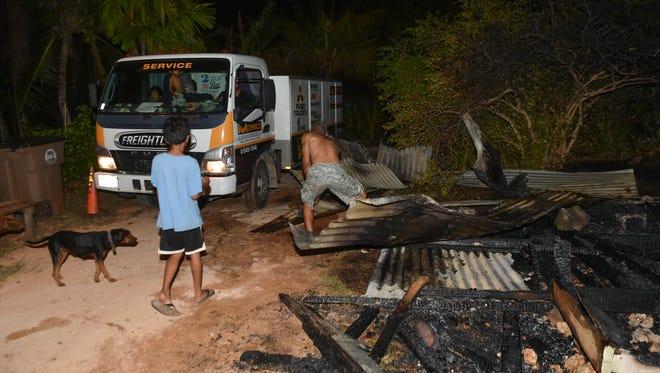 Mangilao resident John Edward Borja clears debris after a structure fire in Mangilao on April 24.