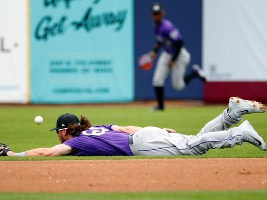 Colorado Rockies' Brendan Rodgers misses a play on a base hit by Milwaukee Brewers' Lorenzo Cain during the first inning of a spring training baseball game Saturday, March 10, 2018, in Phoenix. (AP Photo/Matt York)