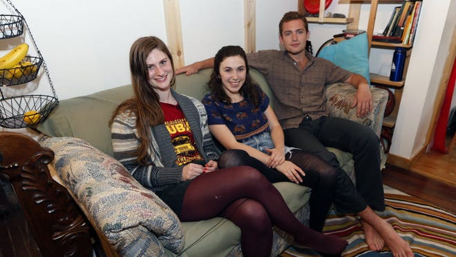 From left, Lara Russo, Cally Guasti and Reese Werkhoven sit on a couch in their apartment in New Paltz, N.Y. on Thursday, May 15, 2014. The roommates had purchased it at a Salvation Army store and found $40,800 stashed inside. After finding a deposit slip, they returned the money to the 91-year-old upstate New York widow who had hidden it there.