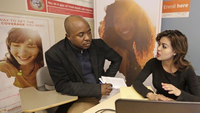 Yvette Calderon explains the new health insurance to David Bilewu in Chicago in February.