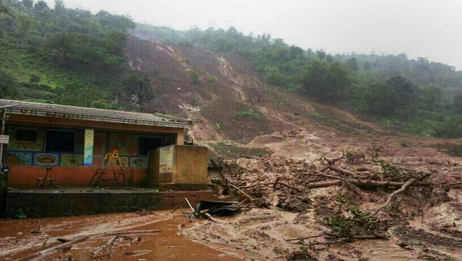 A mudslide surrounds a building in Malin village in the Pune district of the western Indian state of Maharashtra on July 30.