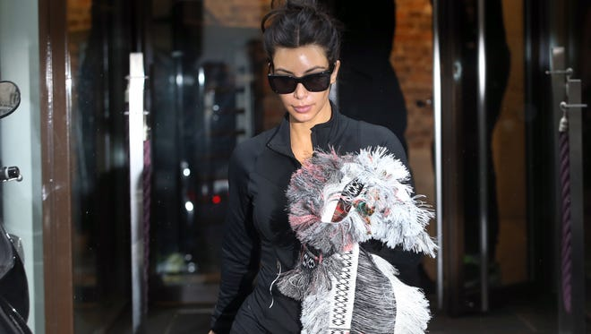 Kim Kardashian walks out of a gym center on May 22, 2014 in Paris. Kardashian and partner US musician Kanye West are expected to be tying the knot this weekend, fuelling speculation about the wedding's location. Florence's La Nazione daily reported that they would have a marriage ceremony in France early on May 24, before travelling to Italy for the party.
