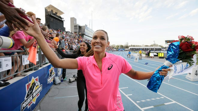 Lolo Jones reacts with fans after running in the women's special shuttle hurdle relay at the Drake Relays athletics meet, Friday, April 25, 2014, in Des Moines, Iowa.