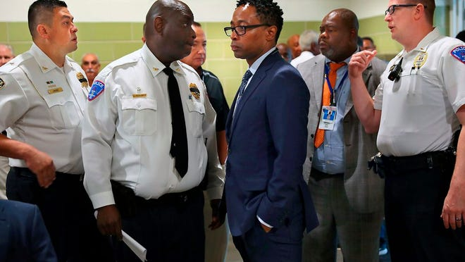 St. Louis County Prosecutor Wesley Bell, center, is surrounded by area police chiefs, including North County Police Cooperative Chief John Buchannan, second left, and St. Ann Police Chief Aaron Jimenez, left, before a news conference about fallen police officer Michael Langsdorf at Beyond Housing on Monday, June 24, 2019 in St. Louis Langsdorf was shot and killed by a man trying to pass a bad check at Clay's Wellston Food Market.