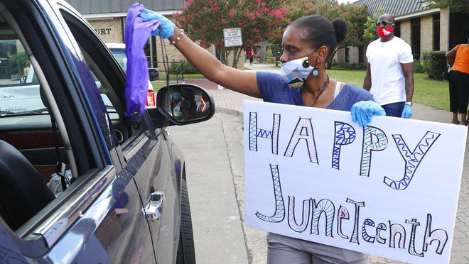 Kim Gardner distributes an aid bag during a drive through Juneteenth 2020 celebration in Dallas, Friday, June 19, 2020. Juneteenth marks the day in 1865 when federal troops arrived in Galveston, Texas to take control of the state and ensure all enslaved people be freed.