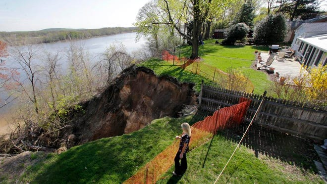 Lynne O'Dell stands near a safety fence in her neighbors' backyard in Florence. Engineers are going to evaluate the landslide that has left O'Dell's home, right, and her neighbors' home on the brink of falling into the Delaware River. Erosion has been a problem for several years to homes on East Front Street in Florence. But the recent rain has created a hole that is growing larger. The O'Dells suspect an old sewer system that runs from the street into the river 70 feet below is to blame.