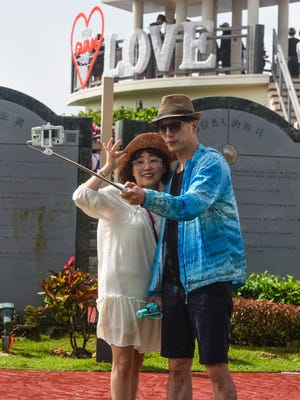 Tourists take a selfie at Puntan Dos Amantes, or Two Lovers' Point, in this Feb. 14 file photo.
