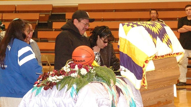 A.J. Longsoldier's parents, Allen John Longsoldier Sr. and Dayna Jean Bear, pay their last respects to their son at his funeral held in the Harlem High School gymnasium.