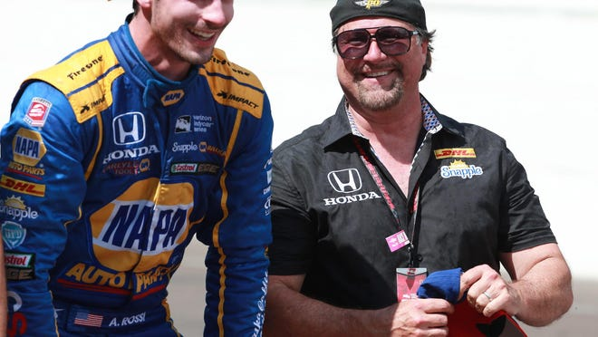 Driver Alexander Rossi, left, and car owner Michael Andretti smile after kissing the bricks following a win at the Indianapolis 500 on Sunday.
