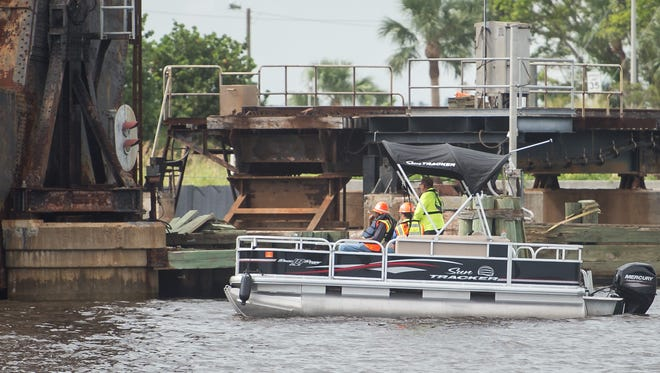 Florida East Coast Railway contractors and inspectors work Oct. 24, 2017, after a barge damaged fenders at the St. Lucie River train bridge in Stuart.