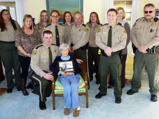 Betty McCoy of Waterloo, seated, is shown with Winneshiek County Deputy Sheriff Steve Nesvik (kneeling) and his fellow officers. McCoy donated $15,000 to the department to help replace police dog Ricky that died from brain cancer.