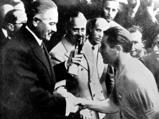 Italy soccer team captain Giuseppe Meazza receives the Rimet Cup at the end of the soccer World Cup Final, in Colombes Stadium, Paris, France, June 18 1938. Italy defeated Hungary by four goals to two in the Final.