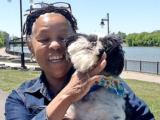 Leslie Palmer stops during a walk with her dog, Shrek, along the Genesee River near the Erie Harbor development, which is adjacent to Corn Hill.