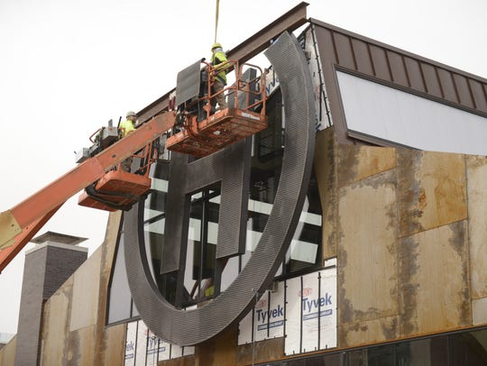Workers install a 4,100-pound sign at Hinterland Brewery