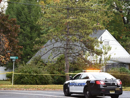 A police car stands guard across the street from a Paramus home where a body was found Tuesday.