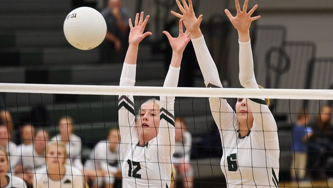 Fossil Ridge High School's Sydni Christopherson and Riley Zuhn block in a game against Columbine High School in regional play last week.
