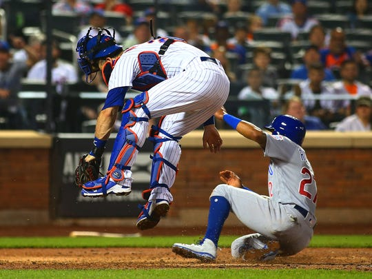 Chicago Cubs shortstop Addison Russell (27) scores on a sacrifice fly against the New York Mets during the seventh inning at Citi Field.