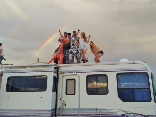 A group of festival goers parties on top of their trailer