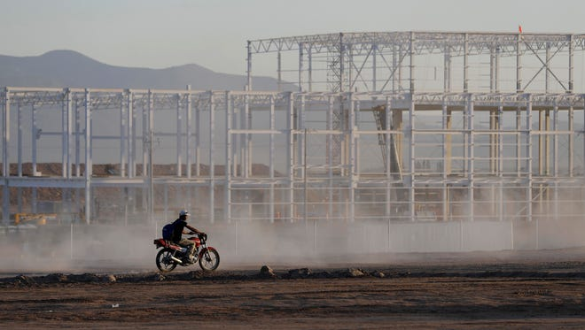 In file photo, a worker at the near-deserted Ford construction site rides past an unfinished building, one day after Ford announced it was canceling plans to build its plant in Villa de Reyes, outside San Luis Potosi, Mexico. Ford said declining sales of small cars, not President Donald Trump, influenced the Mexico plant decision, and the company will still make the Focus in Mexico at a different plant.