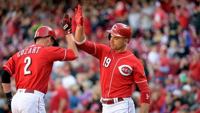 Cincinnati Reds' Zack Cozart (2) and Joey Votto celebrate after Cozart's home run against the San Francisco Giants during the fifth inning of a baseball game Sunday, May 7, 2017, in Cincinnati. (AP Photo/Michael E. Keating)