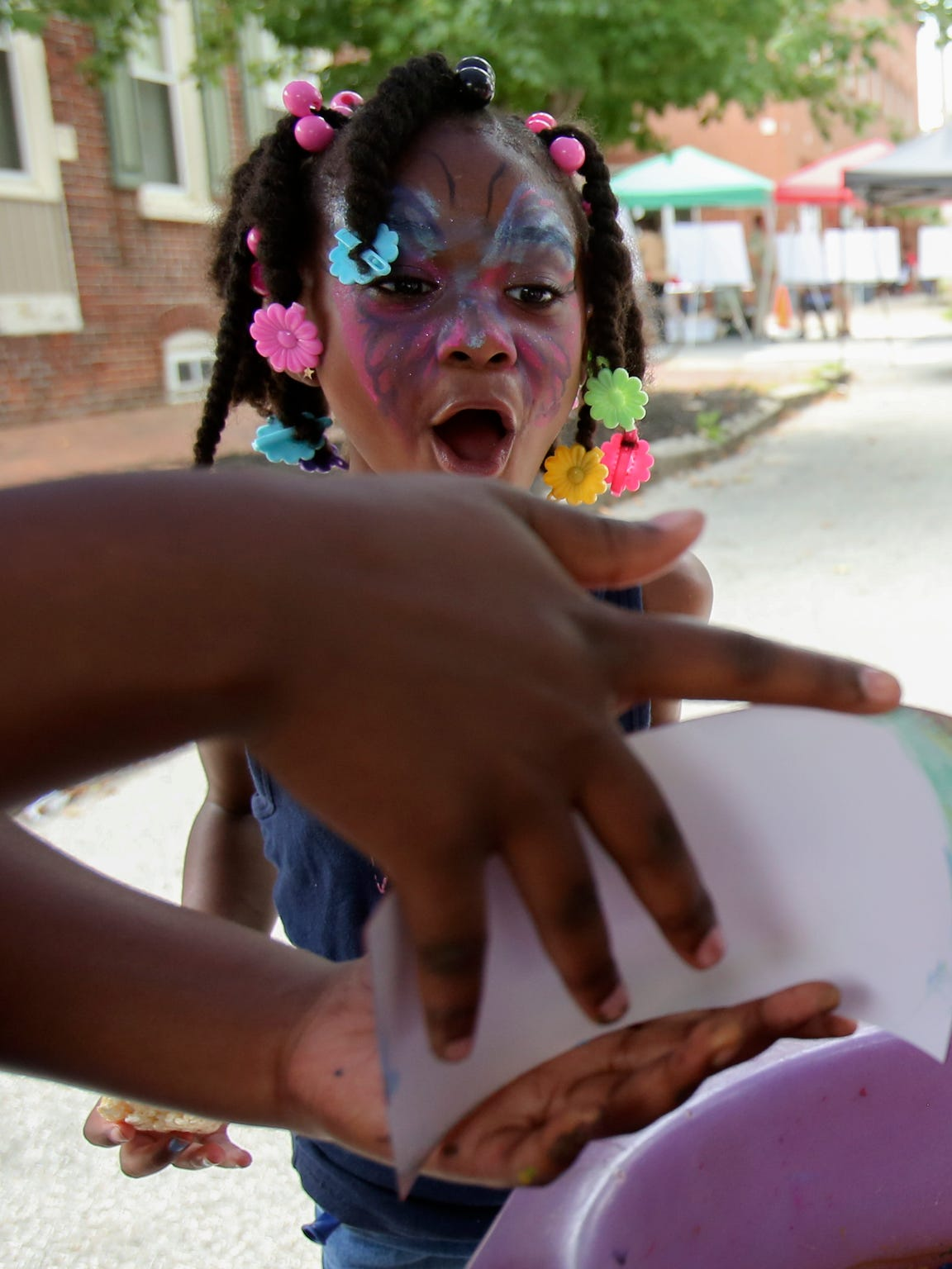 Seanni Pipkins, 6, reacts to her spin art as she is shown the final result she created during Southbridge Community Weekend events in July 2017.
