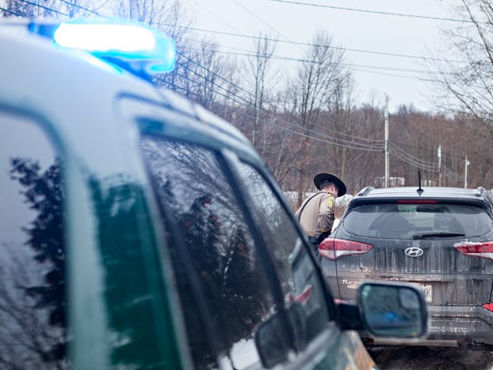 Vermont State Trooper Jay Riggen hands a ticket to