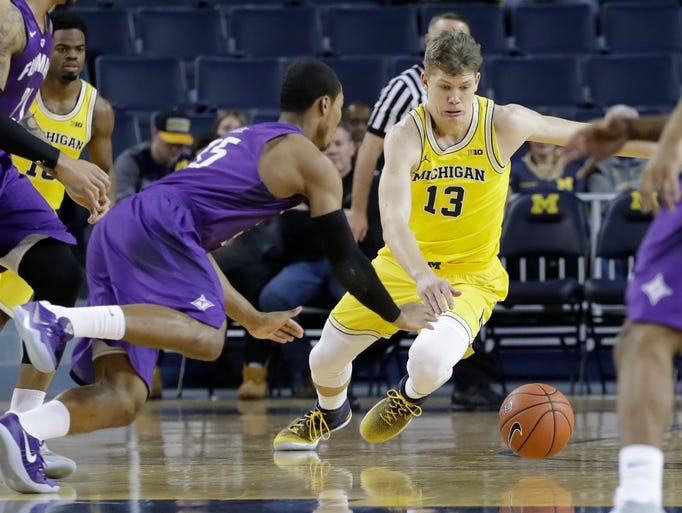 Furman guard Daniel Fowler (35) and Michigan forward