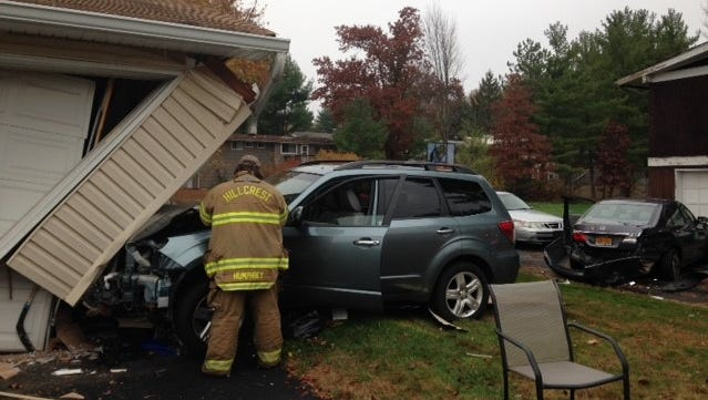 A car hit a school bus and two parked cars then crashed into this house on Southgate Drive in New Hempstead on Friday, Nov. 6, 2015.