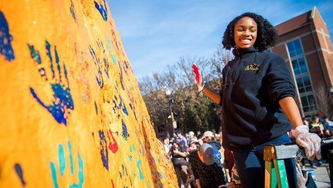 UT sophomore Tiffani Toombs smiles after adding her hand print to The Rock on campus during a gathering on Friday, February 9, 2018, to speak out against recent racist messages painted on The Rock.