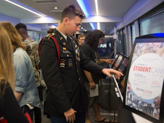 """Cadet Lt. Col. Travis Cetin, of Port St. Lucie High School's Army JROTC, scrolls through information on one of 11 tablets on the traveling C-SPAN bus, sponsored by Comcast, on Nov. 30, 2017, at the school in Port St. Lucie. """"This is a great experience talking about our national history as well as government,"""" Cetin said, who plans to attend Indian River State College before enrolling in the Marine Corps. """"It was my honor to come down here,"""" he said, adding that he will probably get involved in government one day."""