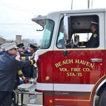 Fire company members push the new pumper into the firehouse.