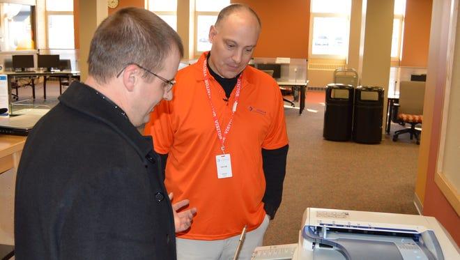 EO Johnson Business Technologies service technician Terry Boneske, left, instructs Wausau Region Chamber of Commerce President/CEO Aaron Kapellusch on copy machine repairs.