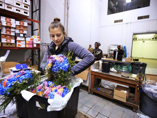 Mary Beth Gearino takes out fresh flowers from a container as they are prepared for delivery at UrbanStems' warehouse in Washington.