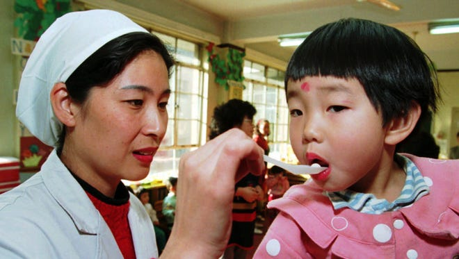 Dr. Lai Nansha uses a spoon to administer a polio vaccination pill to a child at a kindergarten in Beijing.