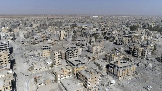 This Oct. 19, 2017 file photo, a frame grab made from drone video shows damaged buildings in Raqqa, Syria.
