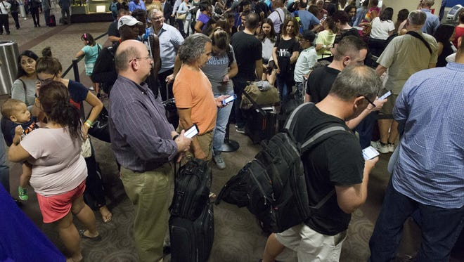 Customers wait in line on Wednesday, July 20, 2016, at Sky Harbor International Airport in Phoenix. Southwest Airlines experienced a computer malfunction Wednesday, causing hundreds of delayed and cancelled flights across the country.