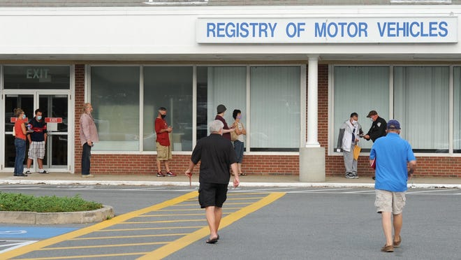 Registry of Motor Vehicle customers in South Yarmouth head from the parking lot to check in with an official outside for an appointment last month.