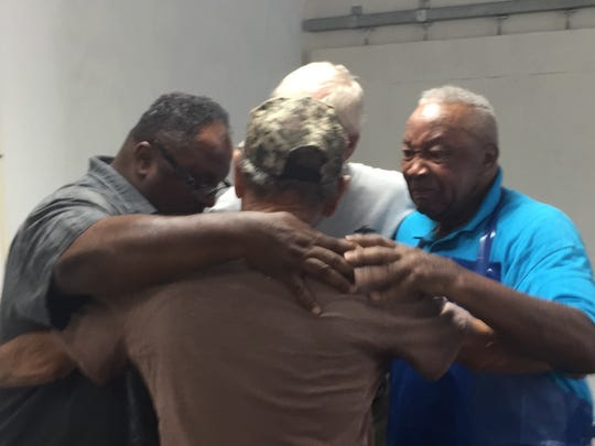 Pastor Scott Sample, left, Clinton PItts, back row, Obediah Sample, right, and Frankie Bennett, front, embrace after the new building housing Nandua Seafood LLC is dedicated in Hacks Neck, Virginia on Wednesday, July 4, 2018.
