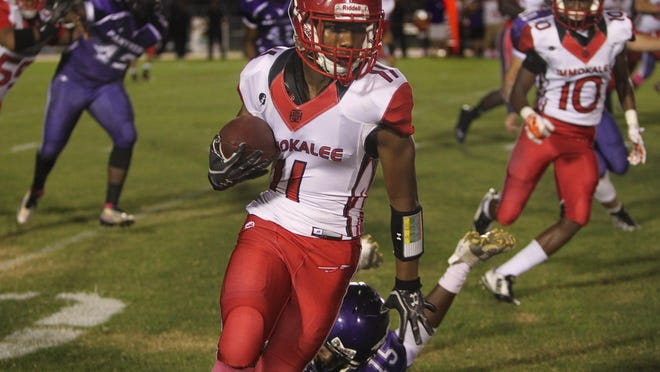 Immokalee running back Malcolm Jackson, center, drags Cypress Lake defender Najir Scott to the ground as the Immokalee Indians visit the Cypress Lake Panthers Friday in Fort Myers.