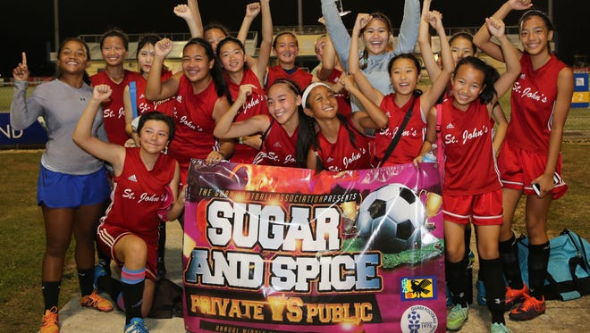 The St. John's School Knights hoist the championship trophy of the 10th Annual Guam Football Association Sugar and Spice Middle School Girls Soccer Festival in celebration after the team's 1-0 win over the Bishop Baumgartner Memorial Catholic School Obispos in the championship match March 4, 2017 at the Guam Football Association National Training Center.