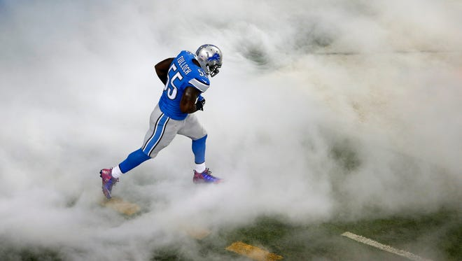 Detroit Lions linebacker Stephen Tulloch runs through smoke while being introduced before a game against the Arizona Cardinals on Oct. 11, 2015, in Detroit.