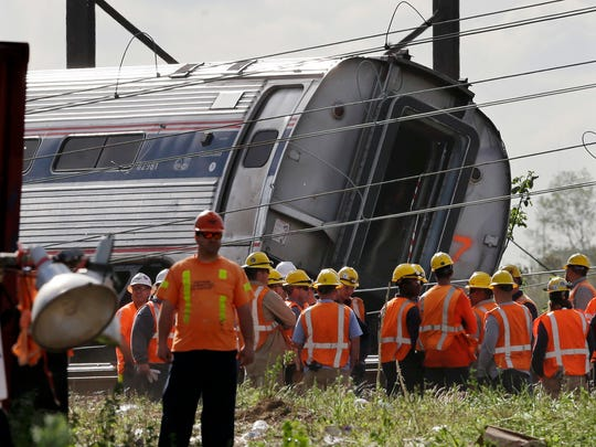 Emergency personnel gather near the scene of a deadly train derailment, Wednesday, May 13, 2015, in Philadelphia. The Amtrak train, headed to New York City, derailed and crashed in Philadelphia on Tuesday night, killing at least six people and injuring dozens of others. (AP Photo/Mel Evans)