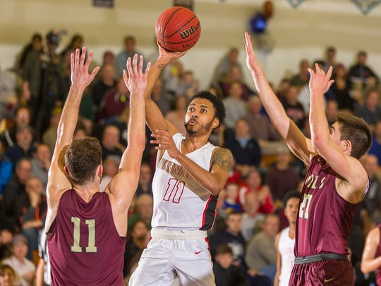Jaylen Colon of Kennedy takes a shot as Joe Cerone, left, and Joey Belli of Wayne Hills defend during the Passaic County boys basketball tournament final. Wayne Hills won in overtime, 55-51 at Wayne Valley High School.