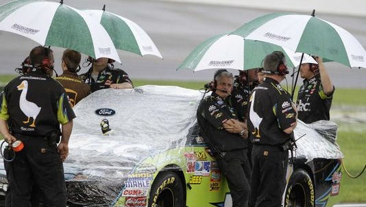 Carl Edwards' crew stands under umbrellas, waiting out the rain during Kentucky Speedway's July 2011 NASCAR weekend.