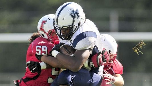 Valley Forge running back Richard Worship is tackled hard by Elyria back Devin Reed the Valley Forge in Elyria, Ohio